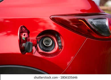 An open fuel tank cap of a red car for filling gasoline or diesel fuel into the gas tank. The back of the car with an open gas tank.