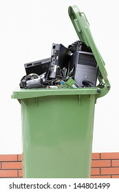 Open garbage bin with electronics on the white background