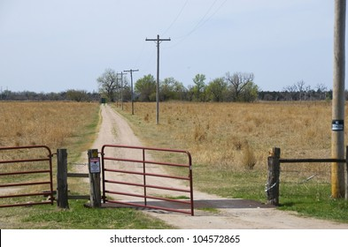 Open gate and lonely little road lead to a family farm on the horizon.  There is a no-trespassing sign on the post to the right.