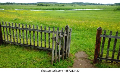 An open gate in a wooden fence and a green meadow beyond it, the path in the frame . Cloudy summer or late spring outside the city