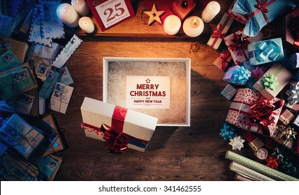 Open gift box with a Merry Christmas and Happy New Year message, presents and Christmas letters all around, desktop top view