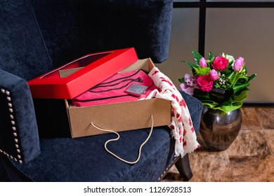 Open gift box on blue armchair with scarf out and flowers in a vase on the floor