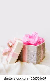 Open gift box with pink ribbon