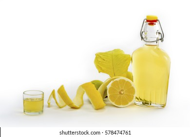 Open glass decanter bottle and shot glass filled with yellow lemon liquor or limoncello or limoncino on white. Peeled natural organic lemon. / Hand Made Lemon Liqueur of Sardinia