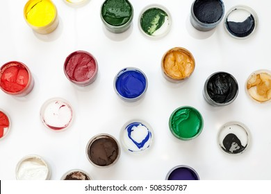 Open gouache jars on a white background, flat lay composition, top view.
