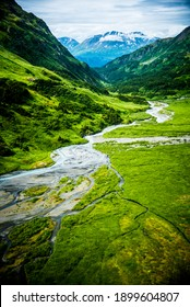 Open green fields in a valley of mountains with streams of rivers flowing through in Alaska taken from a helicopter