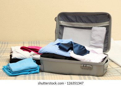 Open grey suitcase with clothing on bed