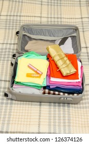 Open grey suitcase with clothing on plaid