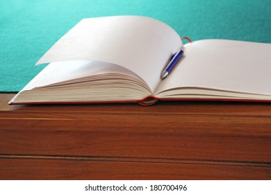 Open guestbook on the table with green cloth