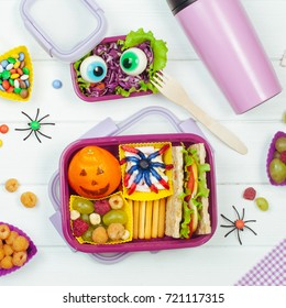 Open Halloween lunch box with school lunch with sandwich, mandarin, snack, berries and chewing marmalade and vegetable salad and thermo mug on white wooden background; top view, flat lay