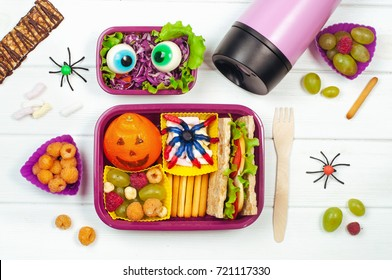 Open Halloween lunch box with school lunch with sandwich, mandarin, snack, berries, chewing marmalade and vegetable salad on white wooden background; top view, flat lay