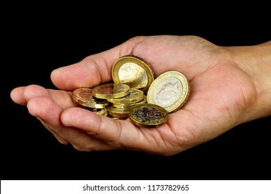 Open hand holding a selection of UK coins isolated on black