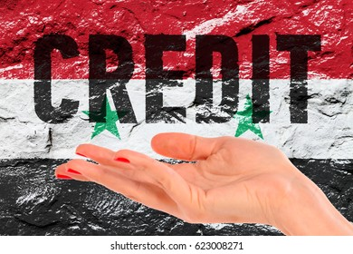 Open hand over flag of Syria and inscription CREDIT on the grunge concrete wall