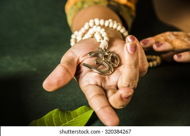 open hand showing Aum locket with beads, green background, facing front
