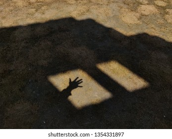 Open hand in window shadow.