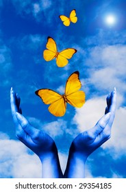 open hands with butterflies flying away in the blue sky