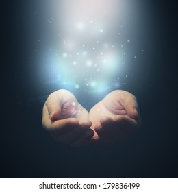 Open hands with magic particles. Holding, giving, showing concept. Selective focus on fingers.