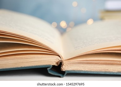Open hardcover book on table against blurred background, closeup