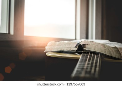 Open Holy Bible on acoustic guitar with sunlight background.