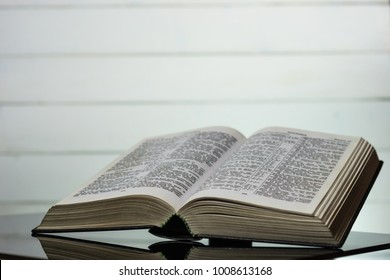 Open Holy Bible on a black glass table. Beautiful White wooden background.Religion concept.