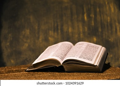 Open Holy Bible on a gold table. Beautiful Gold background.Religion concept.