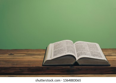 Open Holy Bible on a old oak wooden table.  Green wall background.