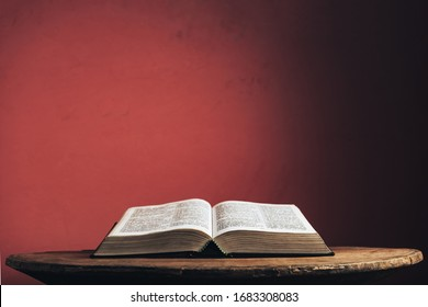 Open Holy Bible on a old brown round wooden table. Beautiful red wall background.