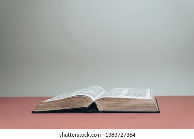 Open Holy Bible on a red table.  Grey wall background.