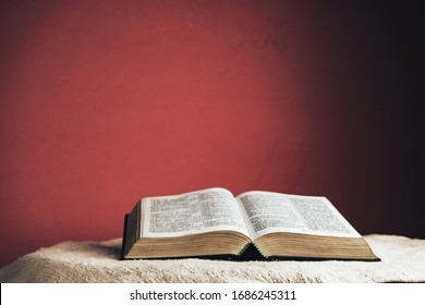Open Holy Bible on a table. Beautiful red wall background.