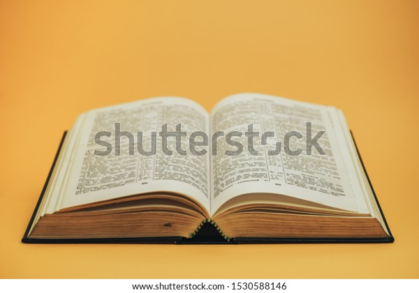 Open Holy Bible  on a yellow background table. Religion concept.