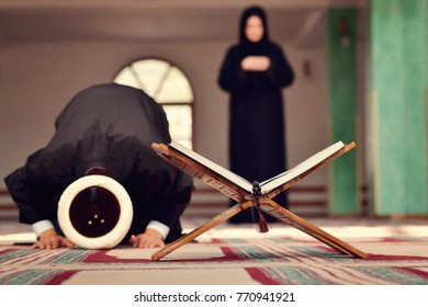 An open Holy quran with wood stand with praying people in background
