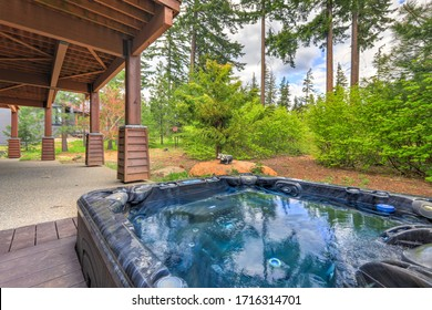 Open hot tub in the back yard with forest and spring and large cabin house with porches.