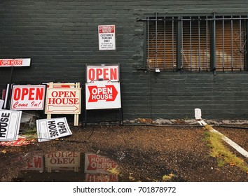 Open house sign board near the wall of a building. Realtors or real estate concept.