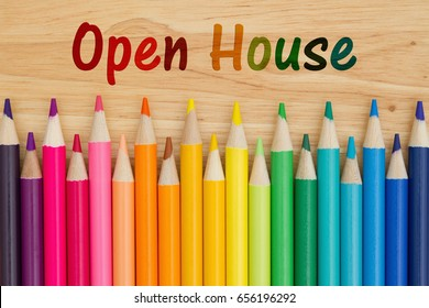 Open House text with colorful pencil crayons on a desk