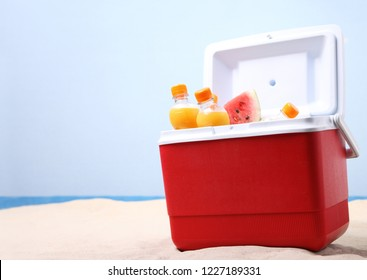Open ice box with orange juice bottles on white sand at the beach