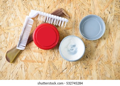 Open jar filled with hair wax with a comb on wood table
