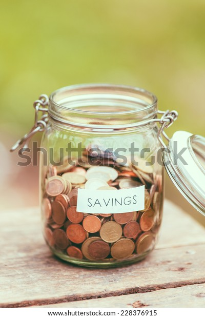 Open jar full of coins with the word saving on a label.
