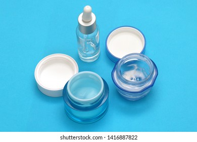 Open jars of cosmetic creams and serums on blue background
