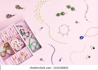 Open jewelry box with neclaces, earrings and rings on pastel background. Top view