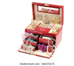 An open jewlery box with gold and platinum  jewelry inside  on a white background