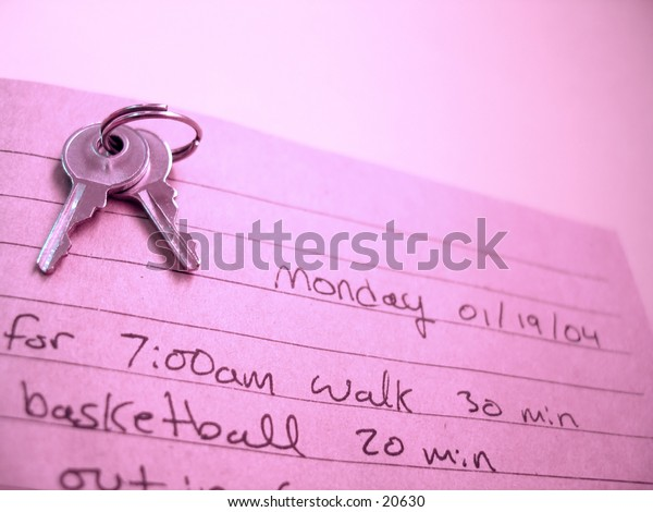 An open journal with a set of keys sitting on the top of the open book. Hand writing inside.
