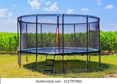 Open Jump Trampoline on green grass near corn field. Outdoor Trampoline with safety net with Zipper entrance.