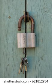 Open with a key padlock hanging on the wooden door