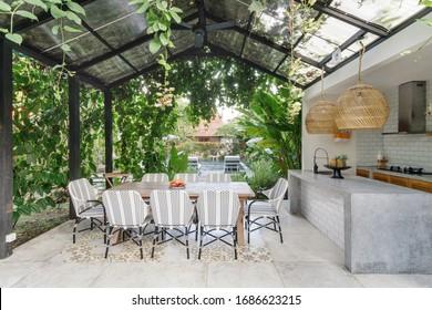 Offene Küche mit Tisch und Stühlen im Esszimmer auf grünem, frischem Hintergrund