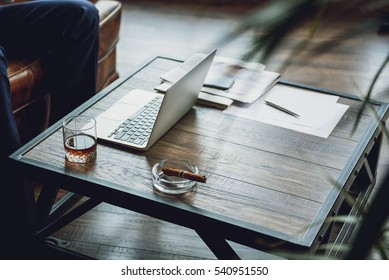 Open laptop and alcohol beverage on desk