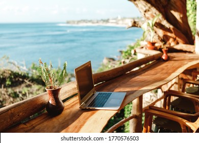 Open laptop with black screen  on wooden table work space outdoors with amazing view on the ocean. Laptop on sea view backdrop