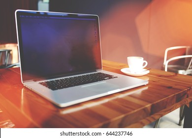 Open laptop computer with copy space screen for text message or advertising content, portable net-book and cup of drink lying on table in contemporary coffee shop interior, freelance work in internet