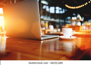 Open laptop computer with space for your brand lying on a wooden table in modern cafe bar interior, portable net-book and cup of hot drink, electronic distance work via internet during coffee break