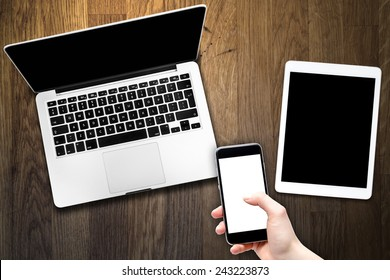 Open laptop with digital tablet and smartphone in hand. All with isolated screen on old wooden desk.