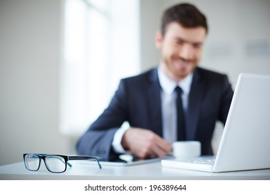 Open laptop and eyeglasses at workplace with businessman on background